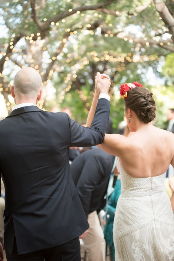Bride and groom raising hands