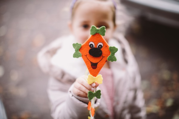 Flower girl holding out face on stick
