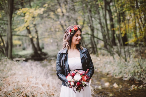 Bride standing by stream in forest