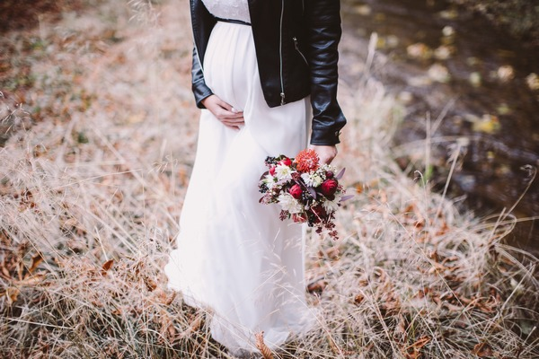 Pregnant bride touching her bump