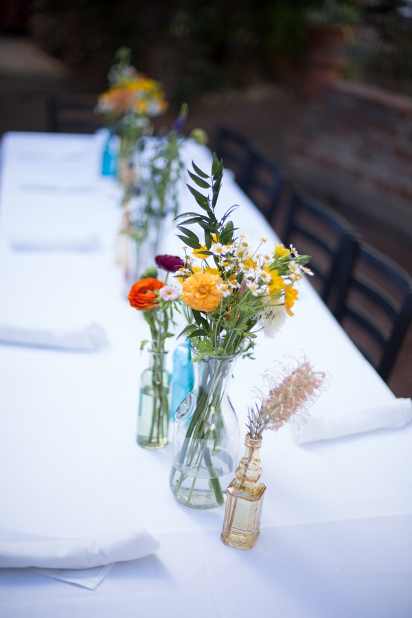 Vases of colourful flowers on wedding top table