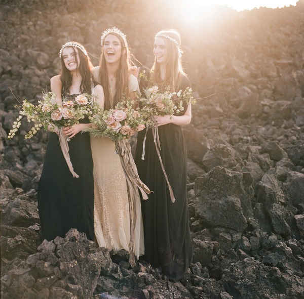 Three boho brides laughing together on rocks