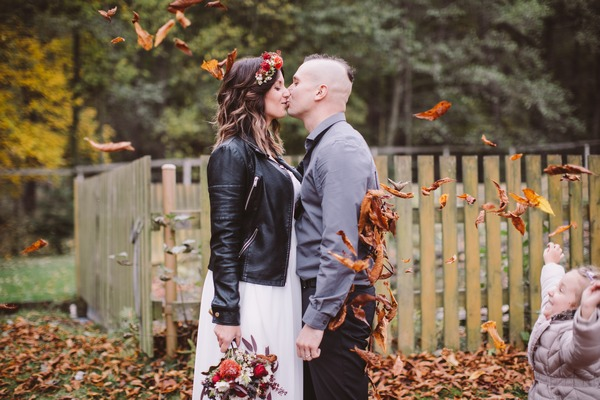 Bride and groom kissing whilst being showered with leaves