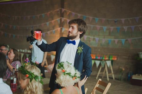 Man raising drink for wedding toast