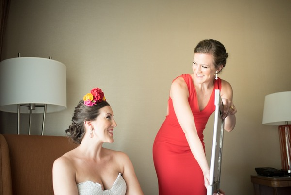 Bridesmaid holding mirror so bride can see herself