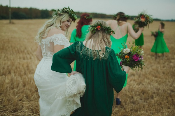 Bride and bridesmaids walking across field