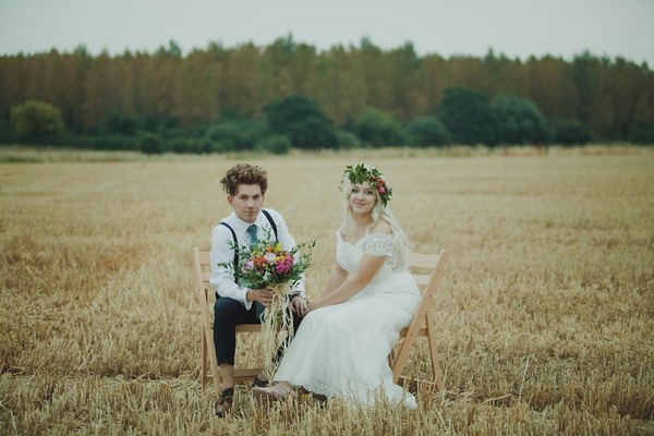 Bride and groom sitting on chairs in corn field
