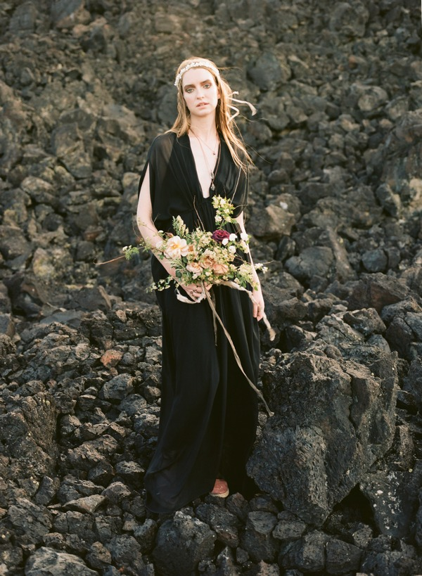 Bride in black dress standing on rocks