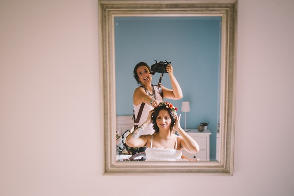 Photographer taking picture of herself and bride in mirror