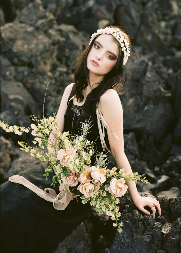 Bride wearing black dress sitting on rocks