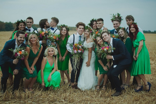 Bridal party posing for picture in a field