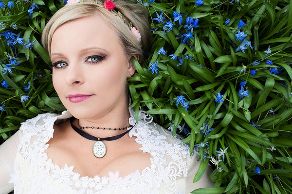 Bride wearing necklaces laying in long grass