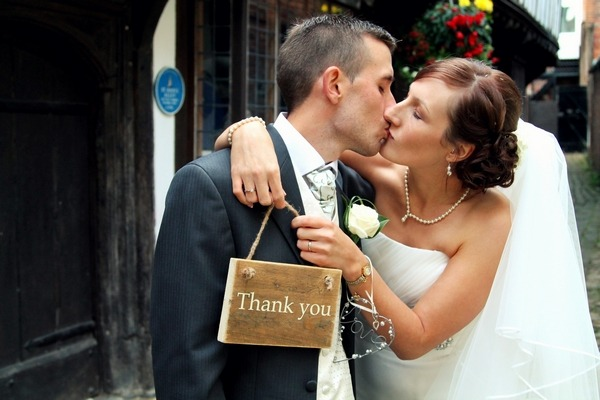 Bride and groom kissing holding thank you sign