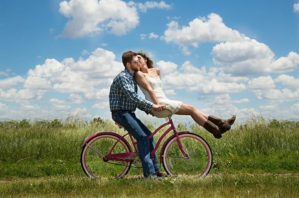 Woman kissing man whilst sitting on handlebars of bicycle