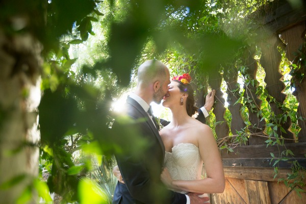 Bride and groom kissing behind branches