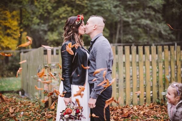 Couple kissing with leaves falling around them