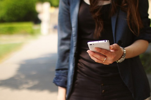 Woman walking looking at phone