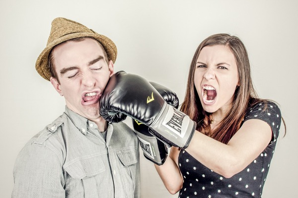 Woman with boxing gloves punching man in face