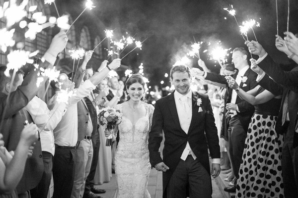 Bride and groom walking past guests holding sparklers
