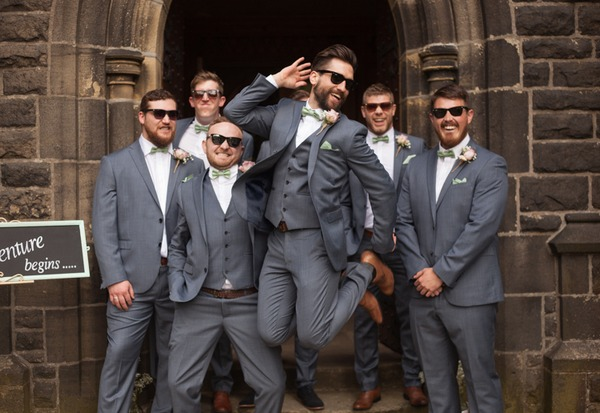 Best man jumping in front of groomsmen