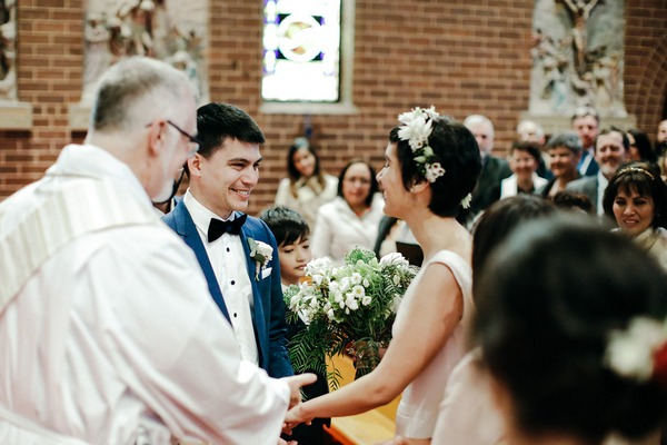 Bride and groom joining hands at altar