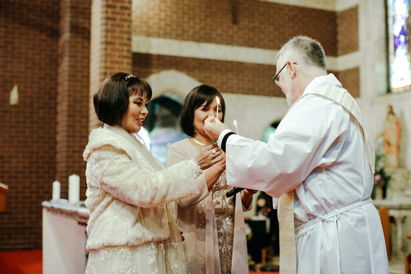 Vicar giving ladies candles at beginning of wedding ceremony
