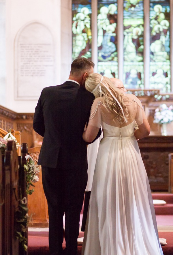 Bride resting head on father's shoulder before he gives her away