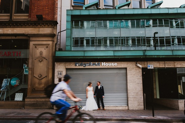 Bride and groom standing in front of shop shutter as cyclist rides by - Picture by Ally M Photography