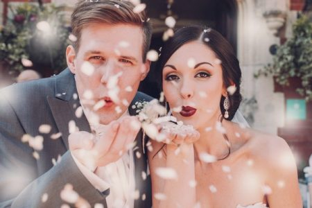 Bride and groom blowing confetti from their hands - Picture by Honeydew Moments