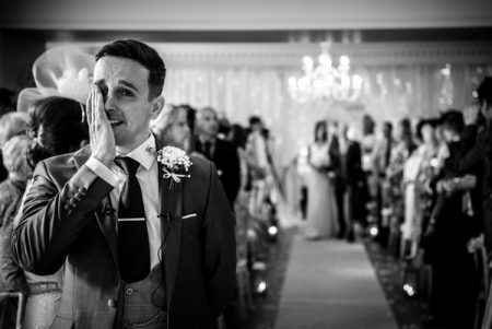 Emotional groom wiping tear from his eye as his bride walks down the aisle - Picture by James Tracey Photography