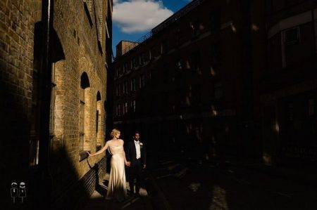 Bride and groom standing between tall buildings - Picture by Paul Joseph Photography