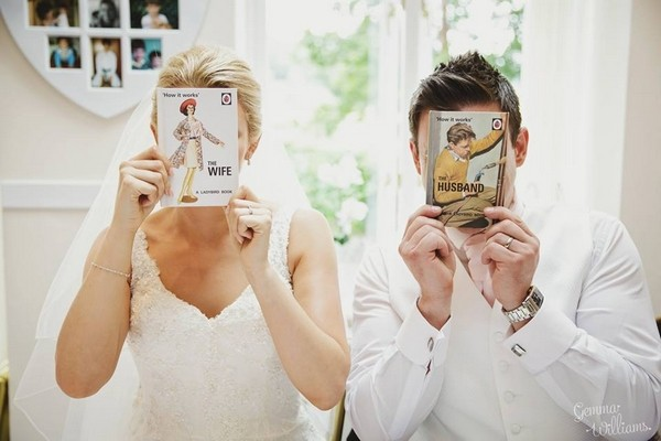 Bride and groom holding husband and wife books in front of their faces - Picture by Gemma Williams Photography