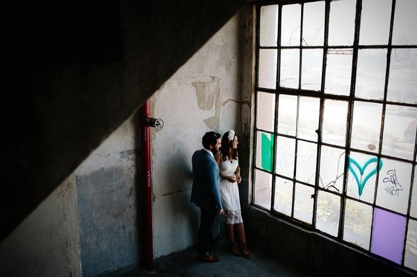 Bride and groom looking out of window of old industrial building - Picture by Claudia Rose Carter Photography