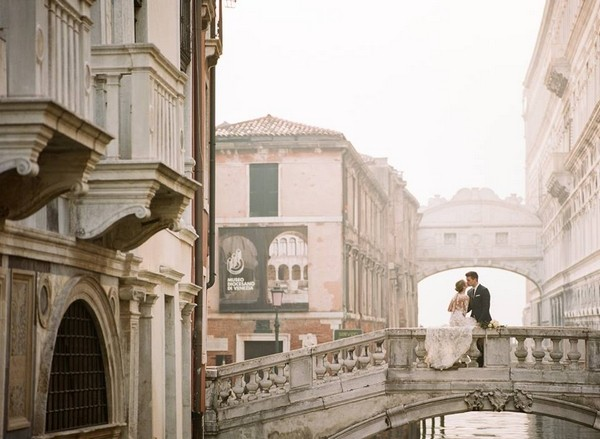 Bride and groom kissing on bridge in Venice