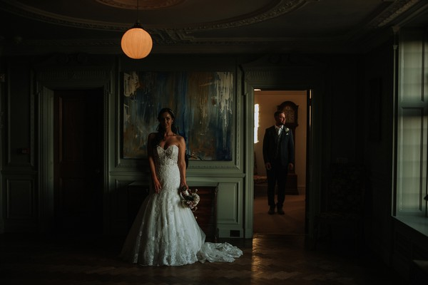 Bride standing in room at Thornton Manor with groom standing in other room seen through open door - Picture by DSB Creative