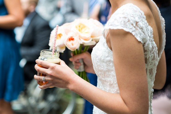 Bride holding drink in jam jar
