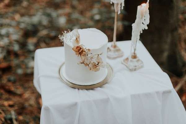 Natural dried flower detail on simple white wedding cake