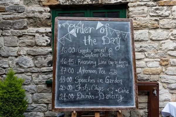 Wedding order of the day written on chalkboard