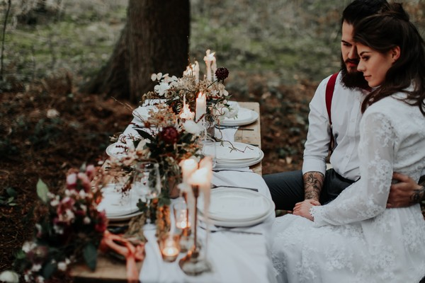 Bride and groom sitting at wedding table in woods