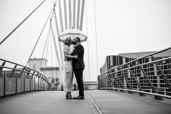 Bride and groom kissing on Manchester Media City Bridge