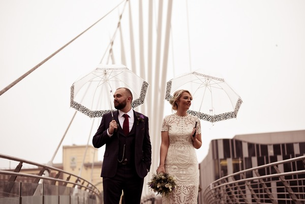 Bride and groom with umbrellas on Manchester Media City Bridge