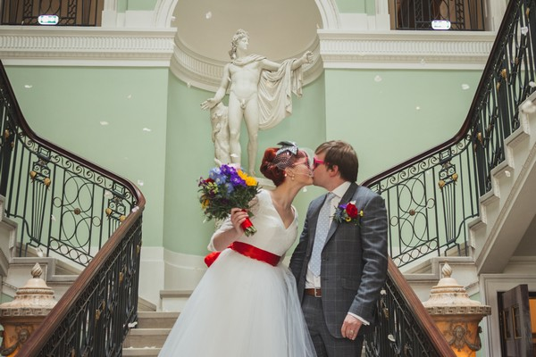 Bride and groom kissing on stairs at Sledmere House
