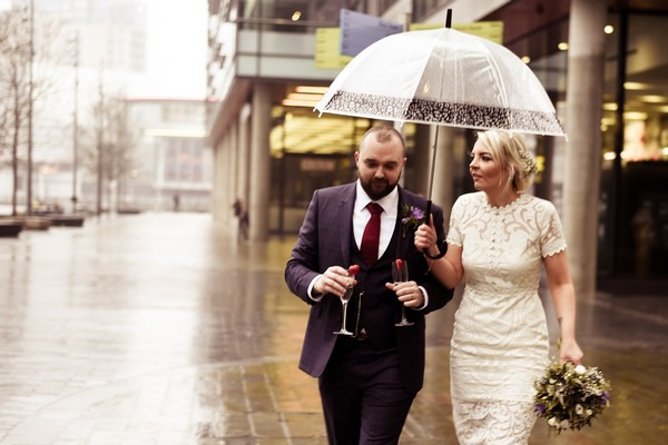 Bride and groom walking in rain with umbrella
