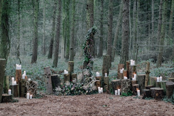 Candles on tree stumps in woods