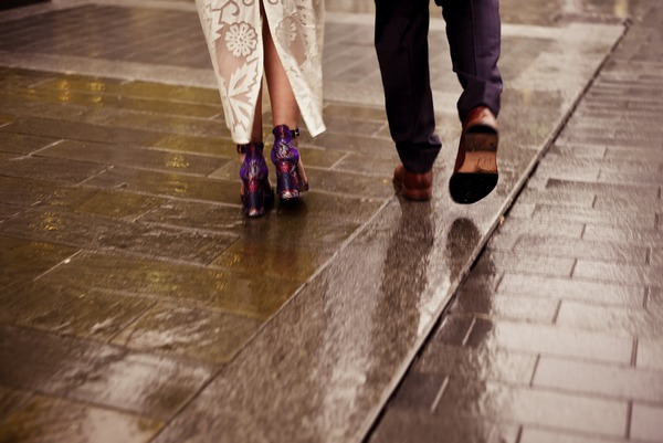Feet of bride and groom walking on wet pavement