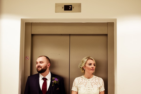 Bride and groom in front of lift at On the 7th