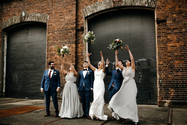 Bridesmaids throwing bouquets in air