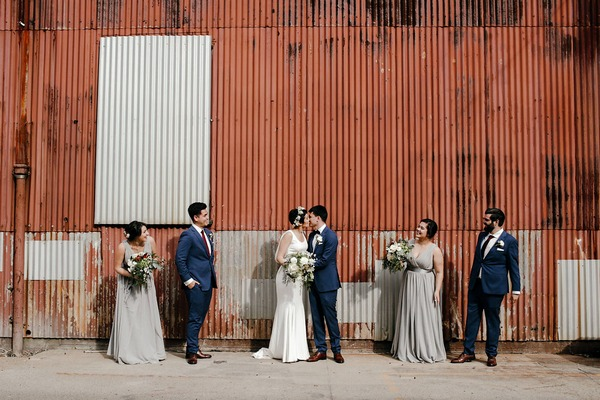 Bridal party watching bride and groom kiss