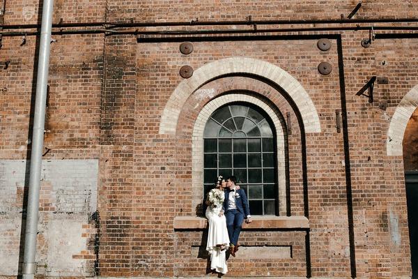 Bride and groom sitting on window ledge