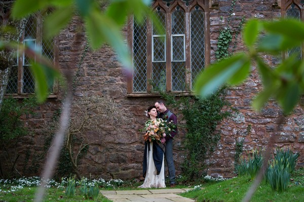 Bride and groom against wall of chapel at Bridwell